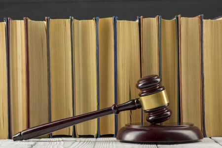 Legal Law concept - Open law book with a wooden judges gavel on table in a courtroom or law enforcement office. Stok Fotoğraf