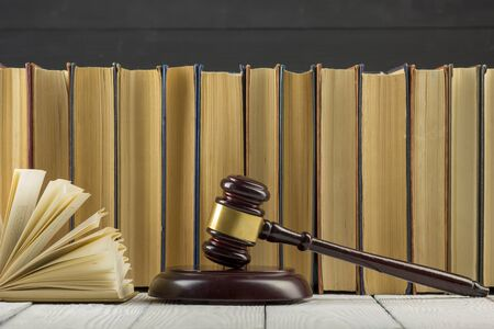 Concetto di diritto legale - Libro aperto di legge con un martelletto di legno dei giudici sul tavolo in un'aula di tribunale o in un ufficio delle forze dell'ordine.