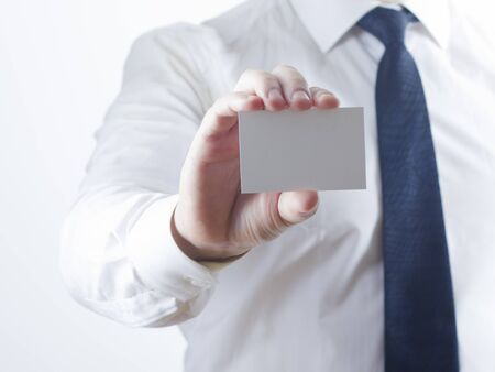 Hand holding white business card on white background