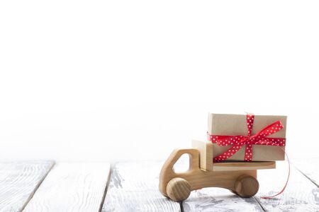 Toy car with Christmas gifts and tree isolated on white backround. Delivery.
