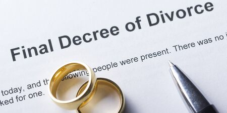 Divorce decree form with marriage ring and pen