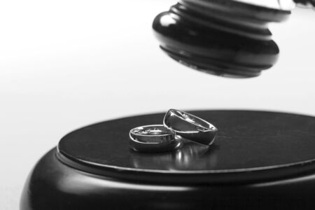Divorce concept. Close up of wedding rings and judge gavel Stok Fotoğraf