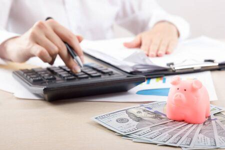 Gros plan d'une femme comptable ou d'un banquier faisant des calculs. Concept d'épargne, de finances et d'économie Banque d'images