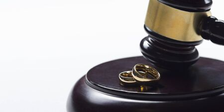 Divorce concept. Close up of wedding rings and judge gavel Stockfoto