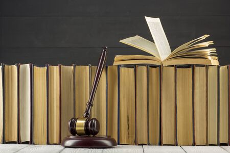Legal Law concept - Open law book with a wooden judges gavel on table in a courtroom or law enforcement office. Фото со стока