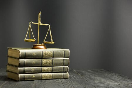 Law concept - Open law book with a wooden judges gavel on table in a courtroom or law enforcement office