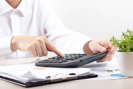 Close up of female accountant or banker making calculations. Savings, finances and economy concept Фото со стока
