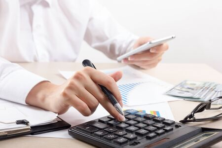 Chiuda in su del ragioniere o del banchiere femminile che effettua i calcoli. Risparmio, finanze e concetto di economia