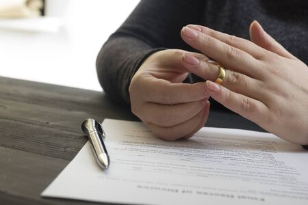 Hands of wife, husband signing decree of divorce, dissolution, canceling marriage, legal separation documents, filing divorce papers or premarital agreement prepared by lawyer. Wedding ring. Foto de archivo