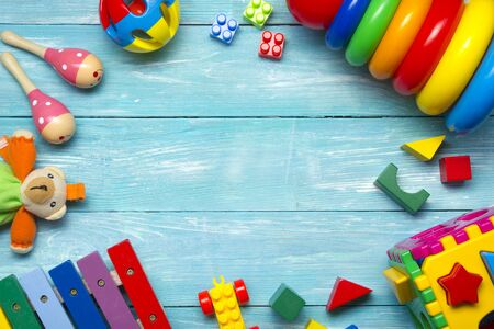 Colorful kids toys frame on wooden background. Top view. Flat lay. Copy space for text. Stock Photo