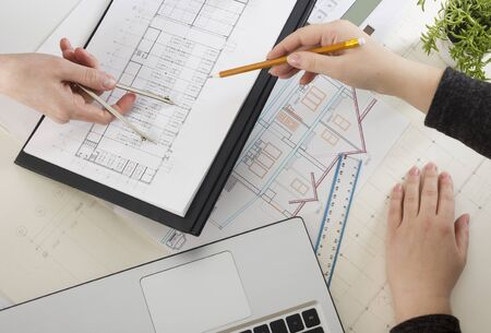 Architects working on blueprint. Architects workplace - architectural project, blueprints, ruler, calculator, laptop and divider compass. Construction concept. Engineering tools. 스톡 콘텐츠