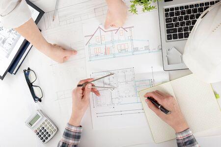 Architekten arbeiten an Blaupause. Architektenarbeitsplatz - Architekturprojekt, Pläne, Machthaber, Taschenrechner, Laptop und Teilerkompaß. Baukonzept. Engineering-Werkzeuge. Standard-Bild