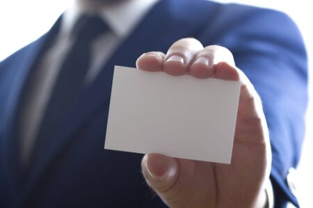Hand holding white business card on white background.