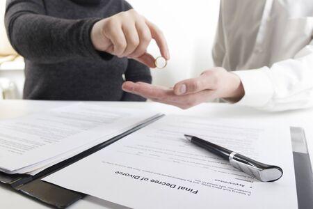Hands of wife, husband signing decree of divorce, dissolution, canceling marriage, legal separation documents, filing divorce papers or premarital agreement prepared by lawyer. Wedding ring. Stok Fotoğraf