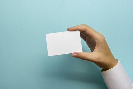 Hand holding white business card on abstract background
