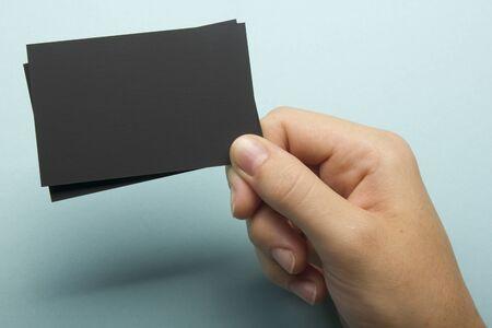 Mano que sostiene la tarjeta de visita blanca sobre fondo abstracto Foto de archivo