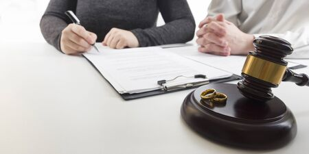 Hands of wife, husband signing decree of divorce, dissolution, canceling marriage, legal separation documents, filing divorce papers or premarital agreement prepared by lawyer. Wedding ring 免版税图像 - 140287649