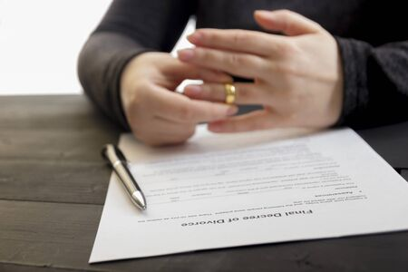 Hands of wife, husband signing decree of divorce, dissolution, canceling marriage, legal separation documents, filing divorce papers or premarital agreement prepared by lawyer. Wedding ring 免版税图像 - 140287724