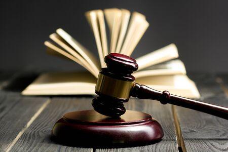 Concetto di legge - libro di legge aperto con un martelletto di legno dei giudici sul tavolo in un'aula di tribunale o in un ufficio delle forze dell'ordine isolato su sfondo bianco. Copia spazio per il testo