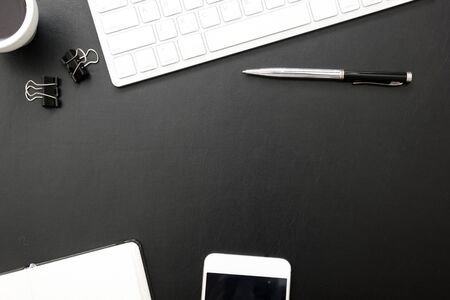 Black desk office with laptop, smartphone and other work supplies with cup of coffee. Top view with copy space for input the text. Designer workspace on desk table essential elements on flat lay