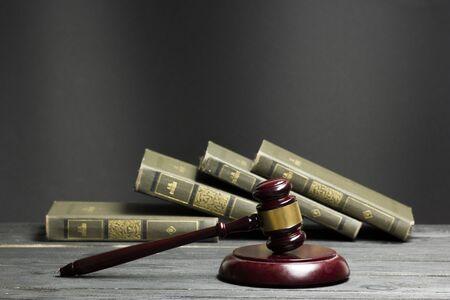 Concepto de derecho: libro de derecho abierto con un mazo de madera para jueces sobre la mesa en una sala de audiencias o una oficina de aplicación de la ley aislada sobre fondo blanco. Copiar espacio para texto