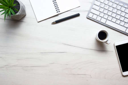 White desk office with laptop, smartphone and other work supplies with cup of coffee. Top view with copy space for input the text. Designer workspace on desk table essential elements on flat lay
