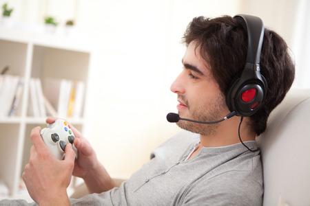 ni�os jugando videojuegos: Vista de un hombre atractivo joven que juega a los videojuegos en un sof� Foto de archivo