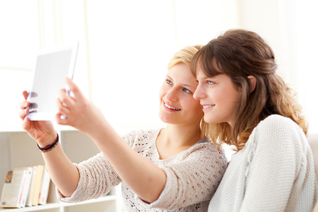 View of Girls on sofa taking selfie picture with tablet Stock Photo