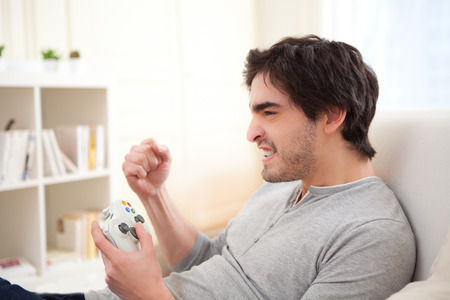 dependance: View of a Young attractive man playing video games in a sofa  Stock Photo