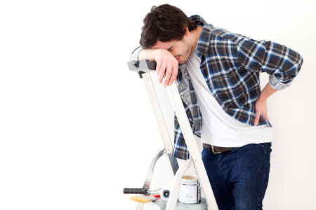 View of a Young man suffering while working on a stepladder photo