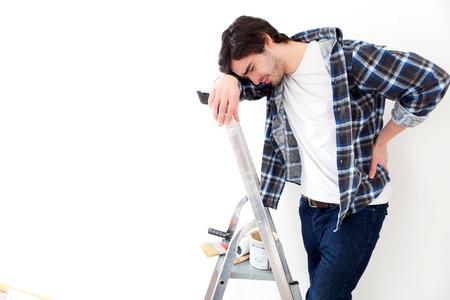 Ansicht der ein junger Mann leidet während der Arbeit auf einer Trittleiter Standard-Bild