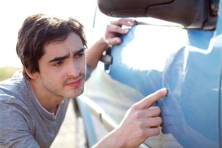 Ansicht eines jungen Mannes Blick auf Kratzer an seinem Auto