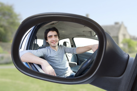 View through the rear-view mirror of an attractive man in his car photo