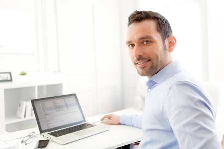 View of a Young business man working at home on his laptop photo