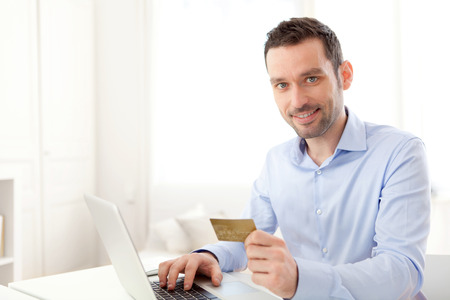 pay desk: View of a Young business man paying online with credit card  Stock Photo