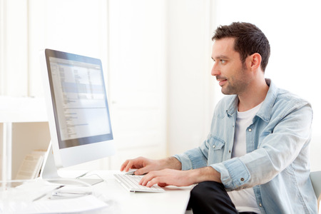 View of a young relaxed man using computer