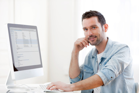 View of a young relaxed man using computer photo
