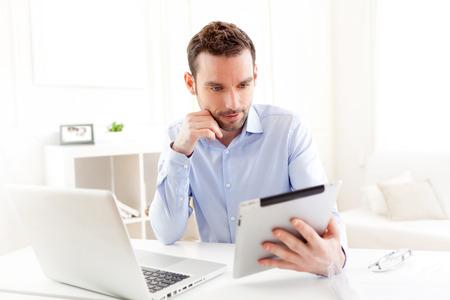 Blick auf einen jungen Geschäftsmann, der zu Hause auf seinem Tablet-