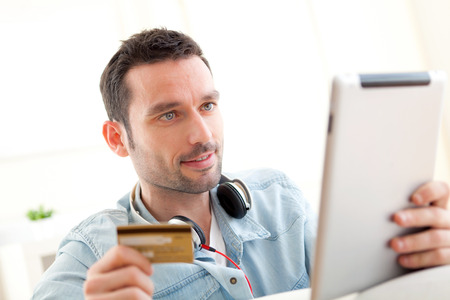 View of a Young relaxed man buying music on tablet photo