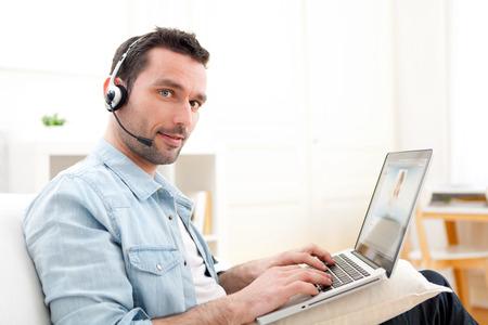 llamando: Vista de un hombre relajado Internet de llamadas de vídeo sobre Young