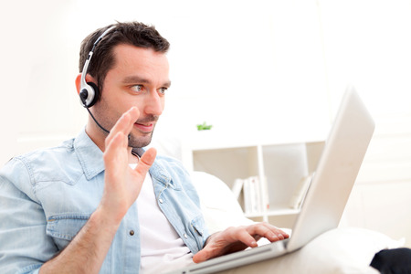 skype: View of a Young relaxed man video-calling on Internet