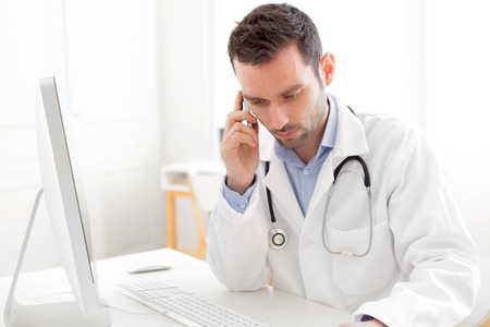 View of a young doctor phoning a patient