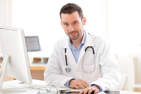 unworried: View of a young smiling doctor in his office Stock Photo