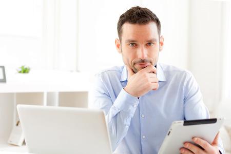 家に彼のタブレットに取り組んで若いビジネスマンのビュー