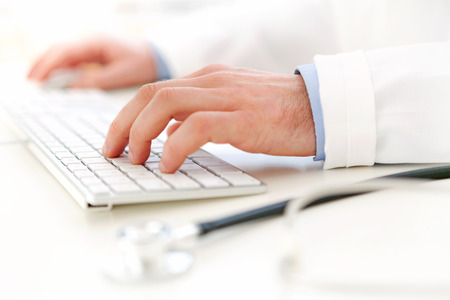 View of Details of doctor hands typing on keyboard photo