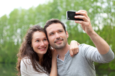 View of a Young couple taking selfie picture at the park photo