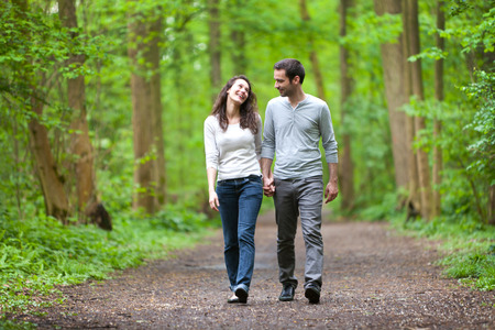 View of a Young couple having a walk in a forest