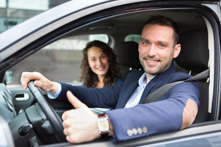 new car: View of a Young business man couple in their brand new car  Stock Photo