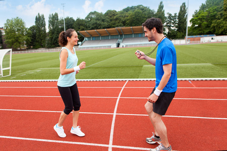 Sport coach training a young attractive woman on a stadium photo