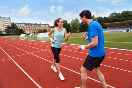 Sport coach training a young attractive woman on a stadium Stock Photo - 29925791